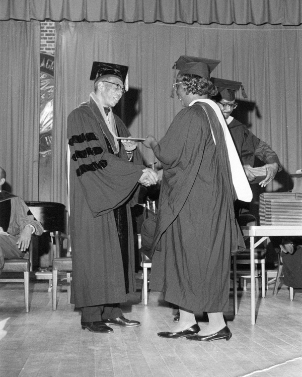 FAMU president Dr. George W. Gore handing diplomas to new graduates in Tallahassee.