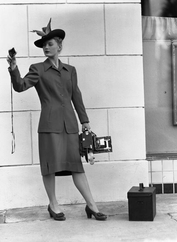 Model holding a Speed Graphic camera while viewing a light meter.