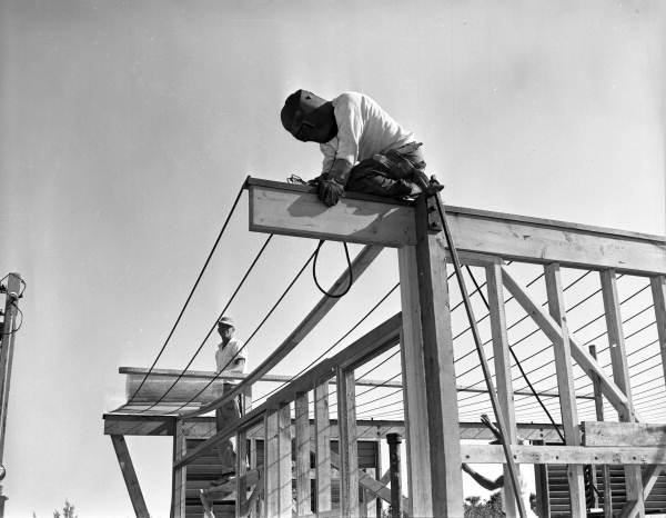 View of a welder at work during construction of Twitchell's cantilever roof house on Siesta Key near Sarasota, Florida.
