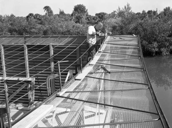View showing a welder at work during construction of Twitchell's cantilever roof house on Siesta Key near Sarasota, Florida.