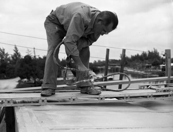 Close-up view showing a worker spraying Cocoon plastic roofing material during construction of Twitchell's cantilever roof house on Siesta Key near Sarasota, Florida.
