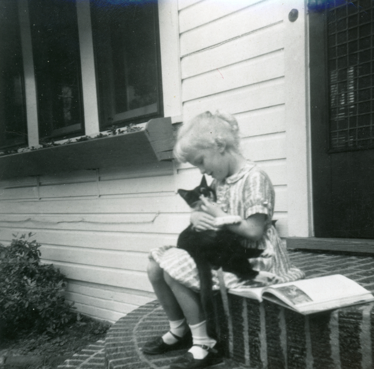 "6-year-old Barbara Byrom with pet cat ""Blackie""."