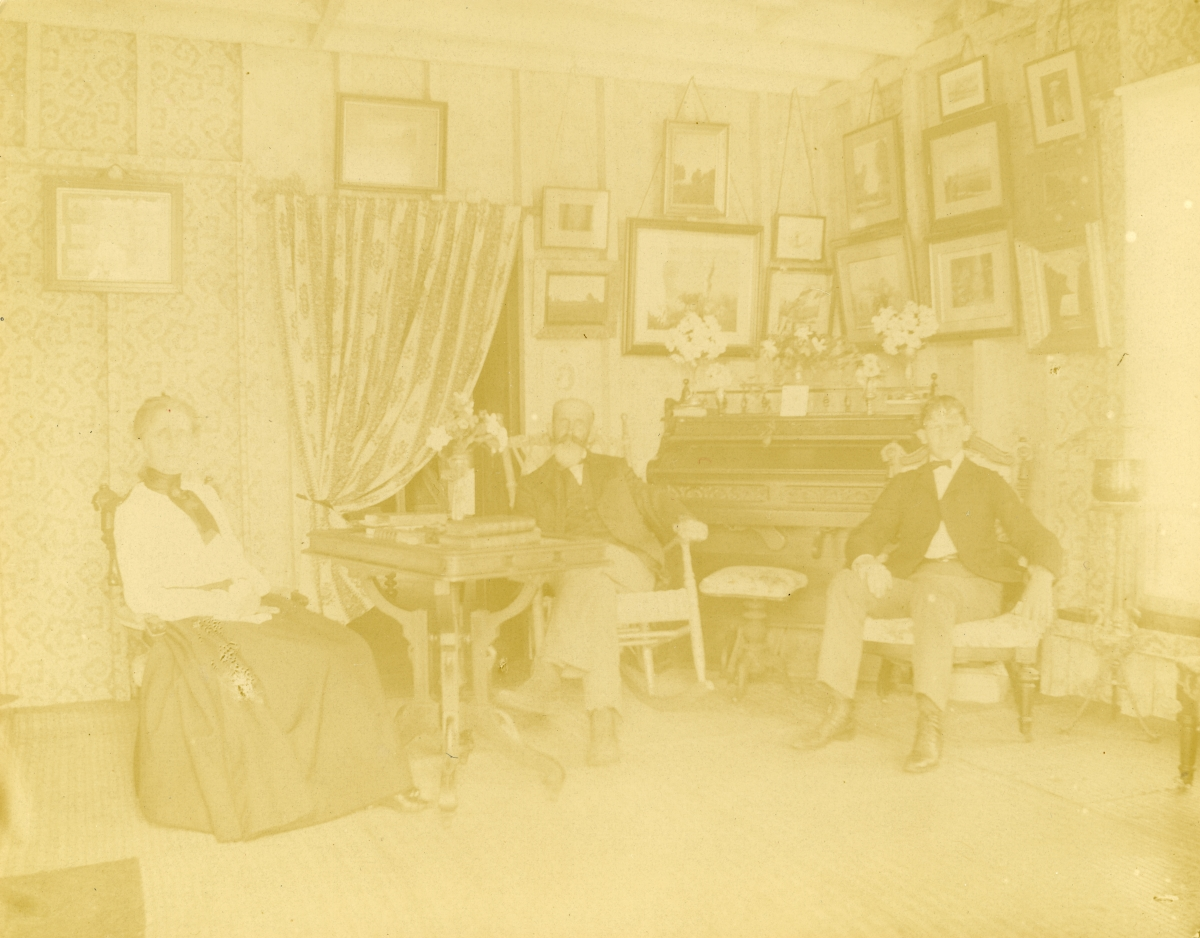 Woman sitting with men inside J. Cook's home - Pomona, Florida.