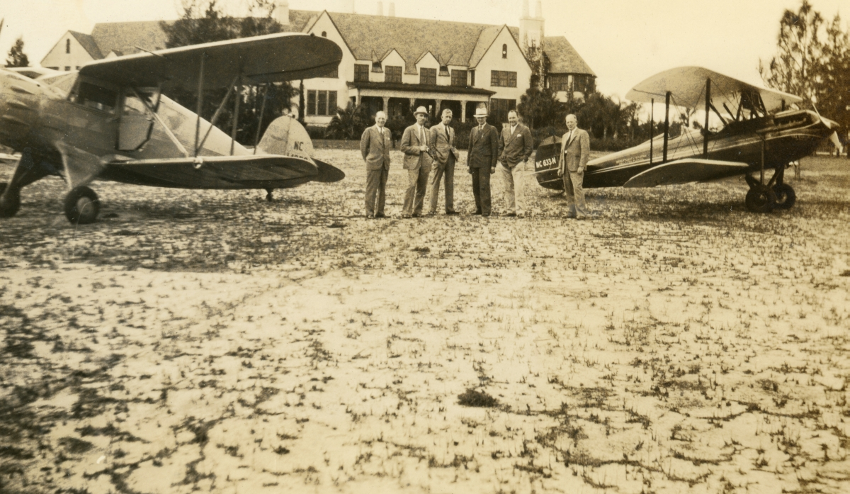 Group of men posing with planes in front of the Mt. Plymouth Country Club during the 2nd annual Orlando Air Party.