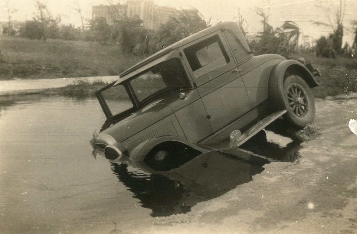 Car blown into damaged road during the 1926 hurricane in Miami Beach.