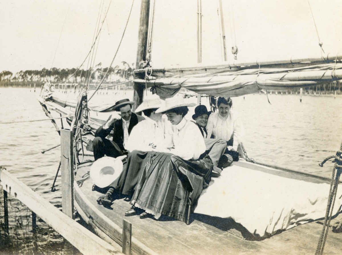 Cassandra Sweeting (foreground) sitting on a boat at dock with friends in Lanark.
