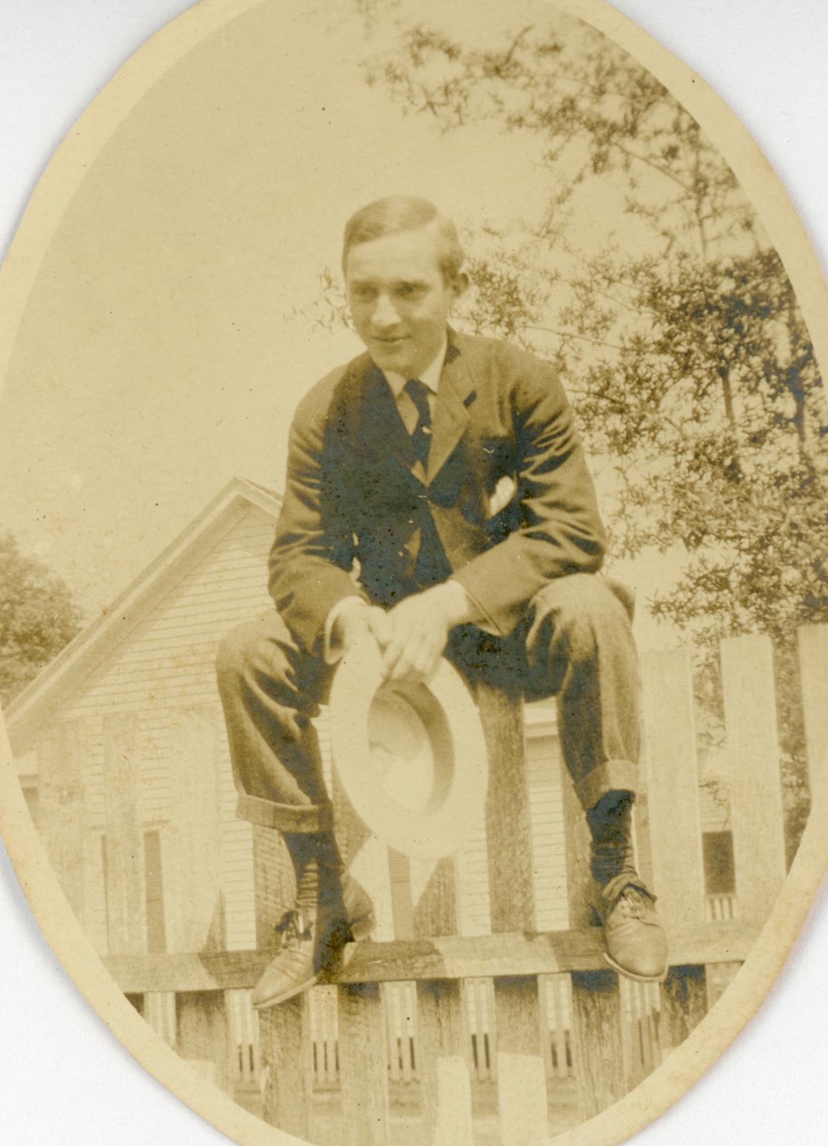 Unidentified man sitting on a fence in Lanark.