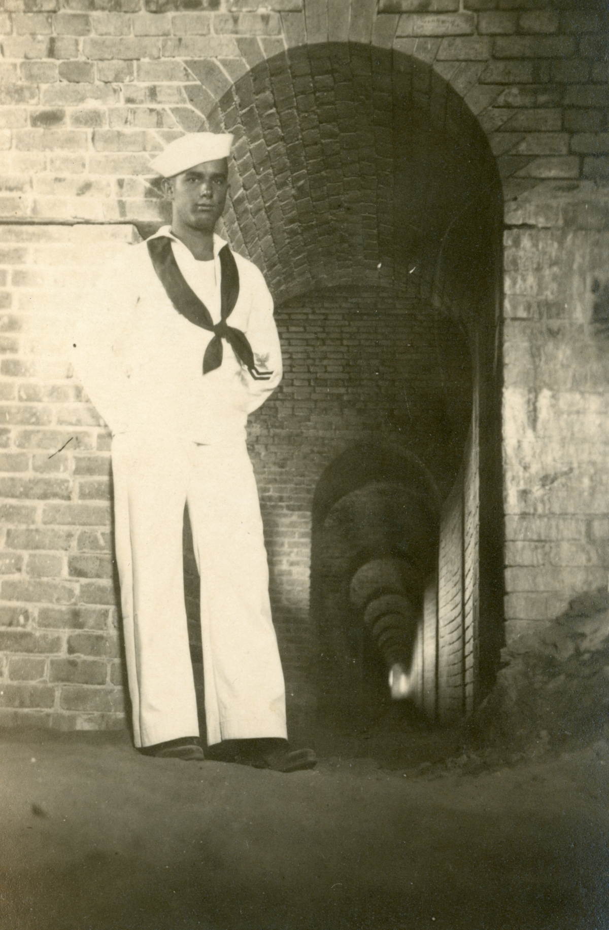Luther W. Coleman posing next to tunnel at Fort McRee.