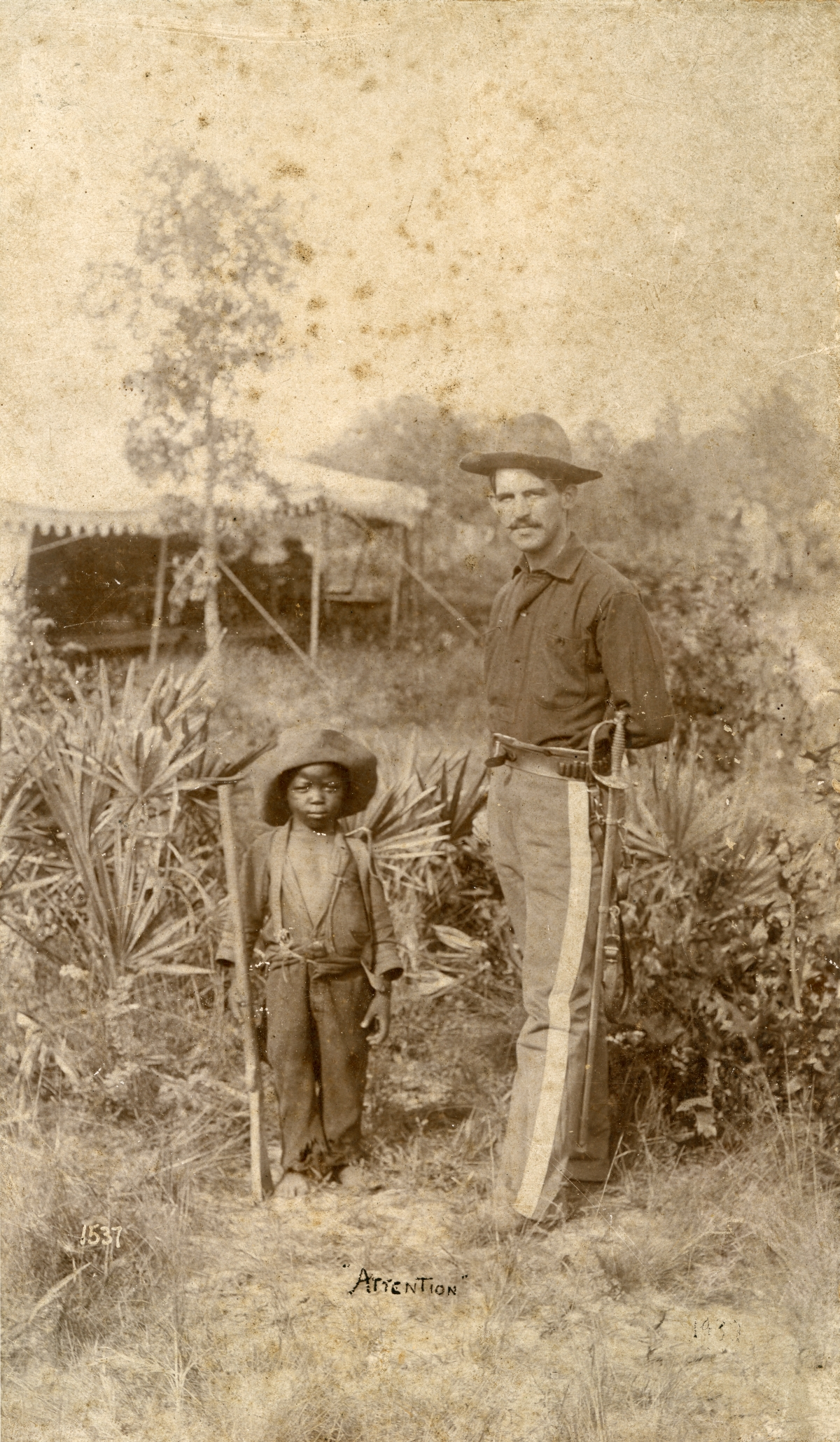 Boy with wooden gun posing with a soldier in Jacksonville.