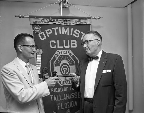 Bob Edenfield, left, retiring president of the Tallahassee Optimist Club turning over gavel to new president Norman Stone.