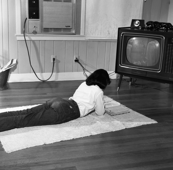 Tallahassee teen reading in front of the t.v.