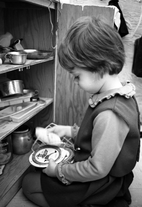 Nursery school child playing with small dishes in Tallahassee.