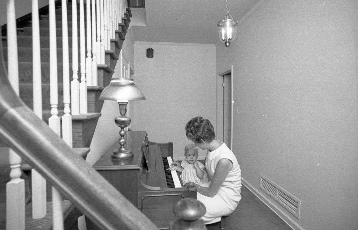 Mother with her child at the piano in their house in Tallahassee.