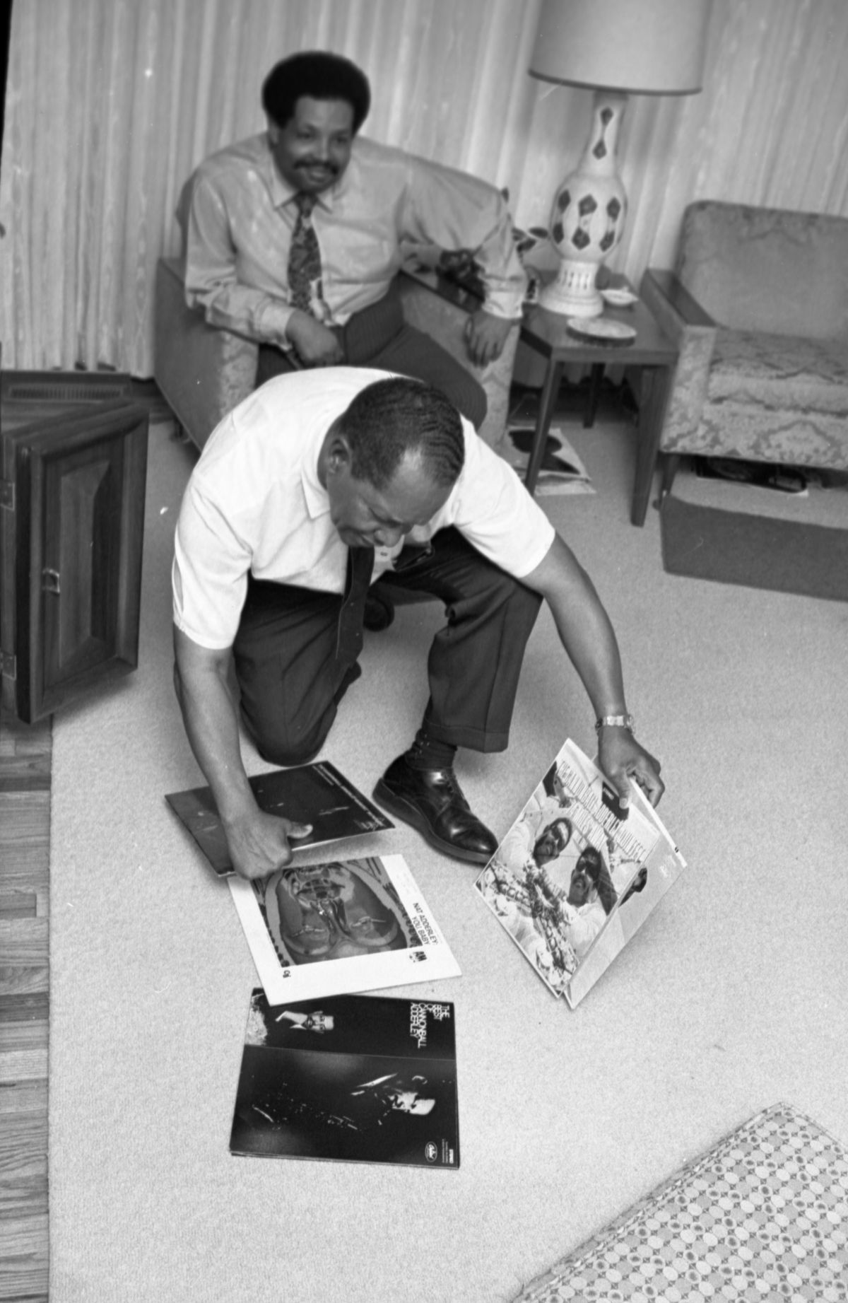 Cannonball Adderley at home with his father J.C. looking at phonograph records in Tallahassee.