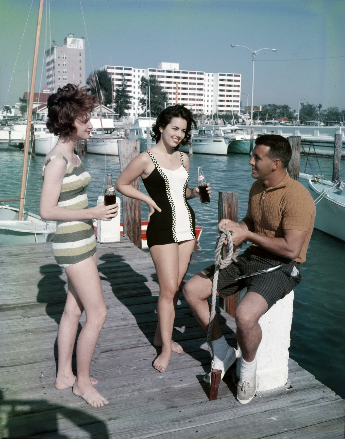 Man with women in bathing suits at a marina in Sarasota.