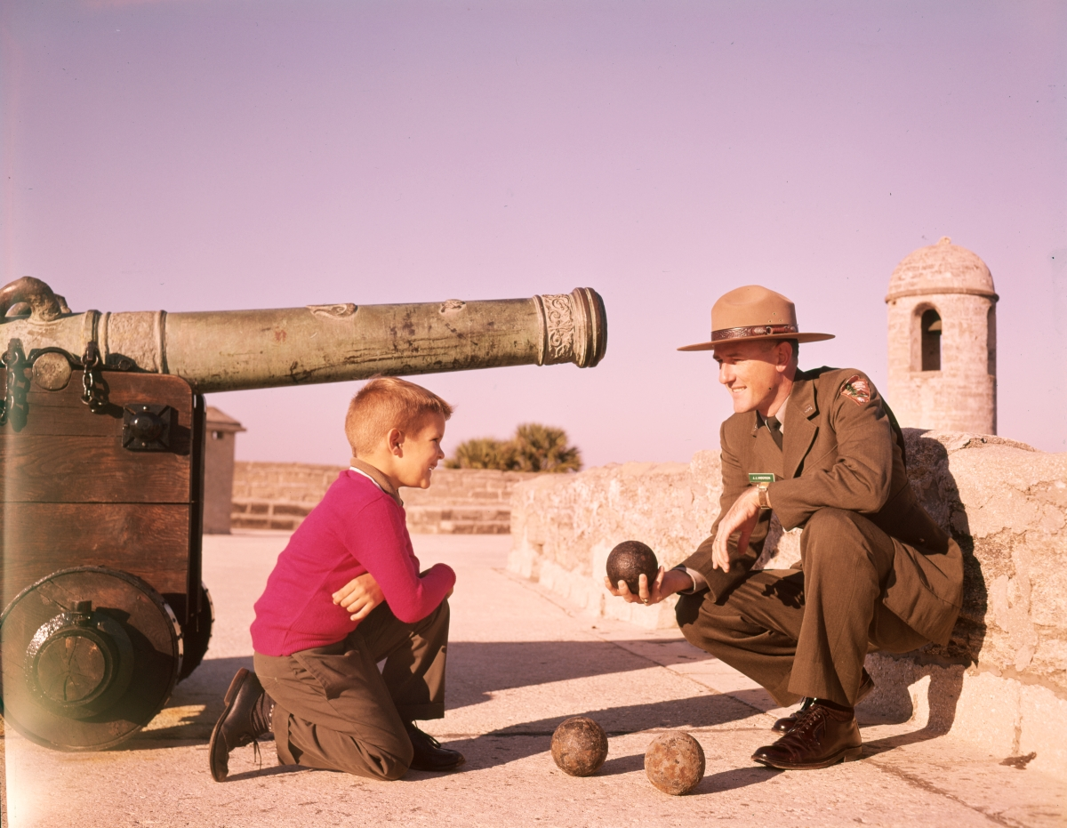 Young visitor listening to ranger J.J. Anderson describe the cannon at Castillo de San Marcos in St. Augustine.