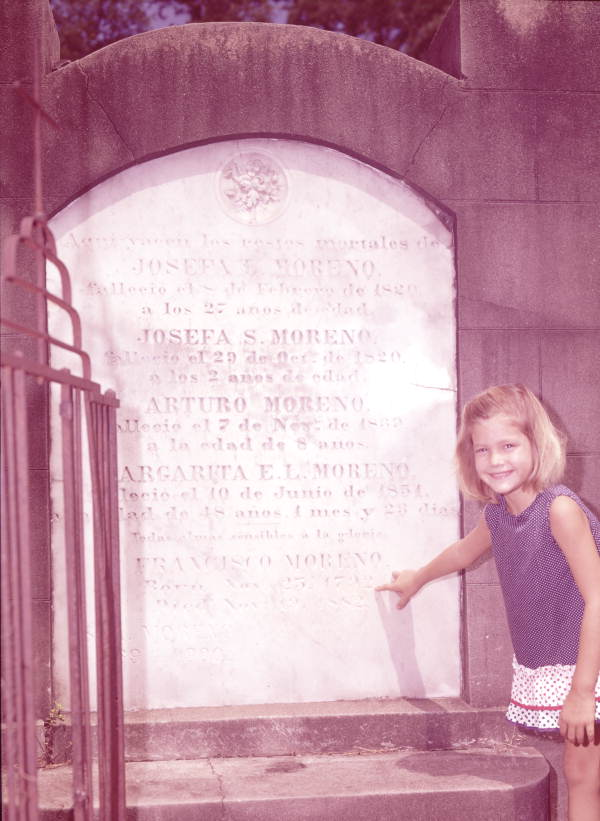 Girl pointing to the Moreno family stone monument at St. Michael's Cemetery in Pensacola.