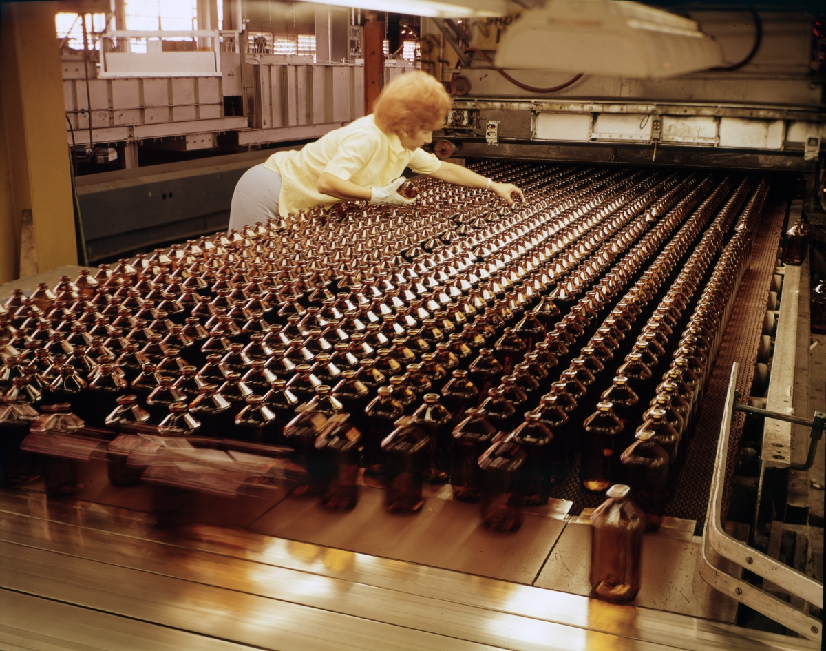 Worker checking bottles on the assembly line at the Thatcher Glass Manufacturing Company in Tampa.