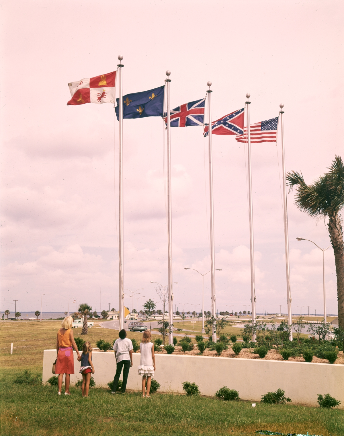 Tourists viewing the five flags of Pensacola.