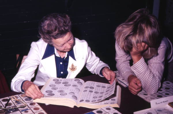 Collectors viewing price book for coins in the Ybor City market.