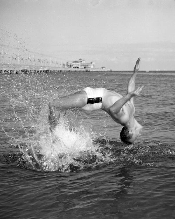 Swimmer doing a backflip in the water.