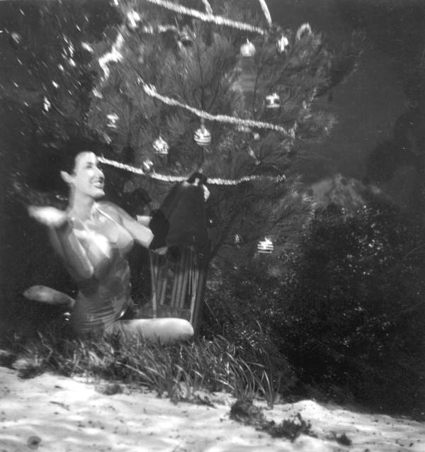 Teresa Myers with pair of flippers she found beneath underwater Christmas tree at Weeki Wachee Springs.