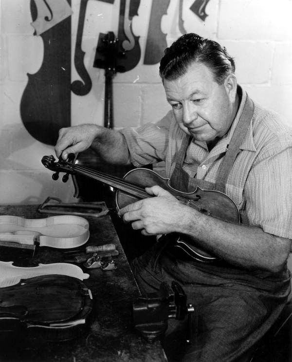 Violin maker Dudley Reed checking a violin for tonal quality.