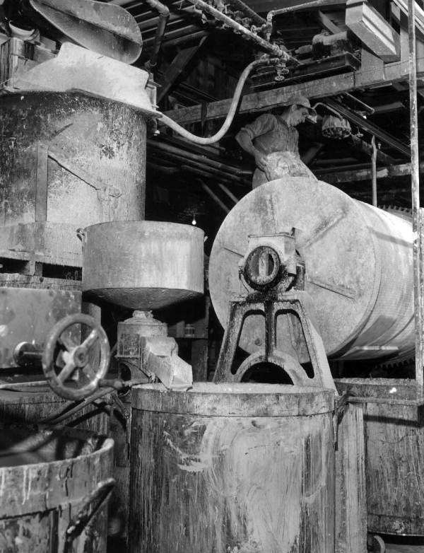 A worker pouring pigment into a grinding mill at the Harris Standard Paint plant - Tampa, Florida.