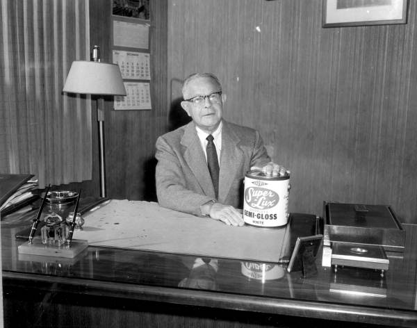 Mr. J. Harris displaying a can of paint in his office - Tampa, Florida.
