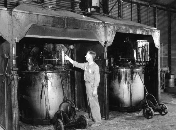 A worker checking a varnish mill at the Harris Standard Paint plant - Tampa, Florida.