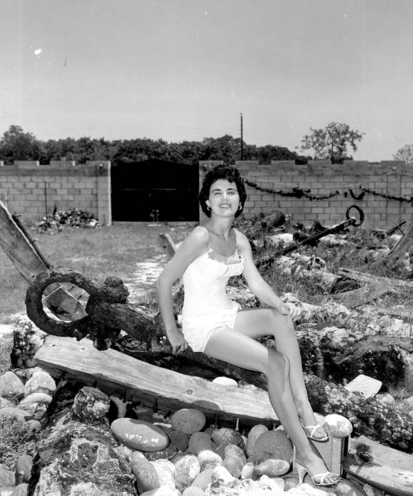 Jackie Sweeting poses on relics displayed outside the McKee's Museum of Sunken Treasure - Plantation Key, Florida