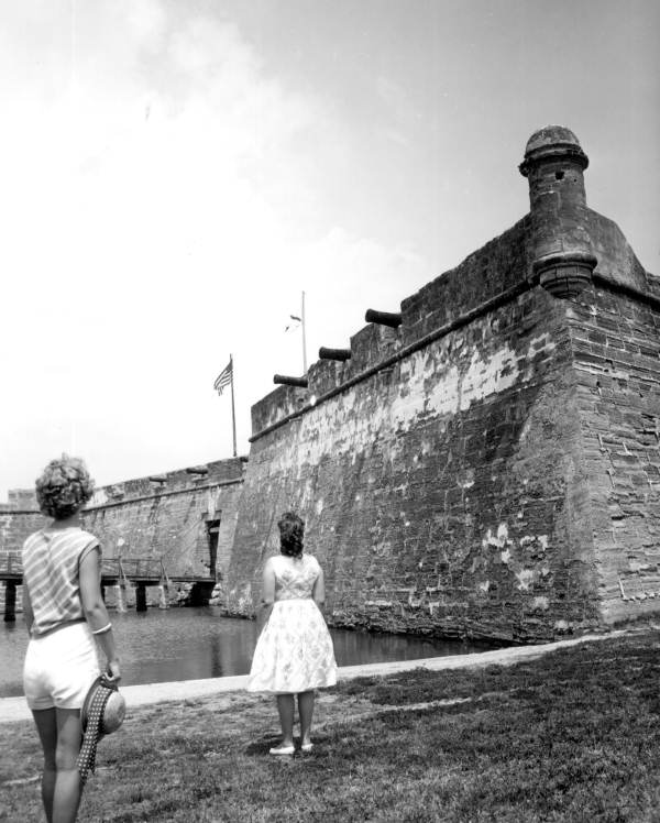 Two young ladies looking up to the bastion from the bank of the moat - Saint Augustine, Florida.