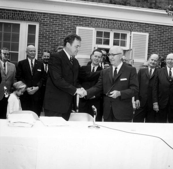 Roy Disney shaking hands with Governor Claude Kirk during the signing of the Disney bill at the Governor's mansion - Tallahassee, Florida.
