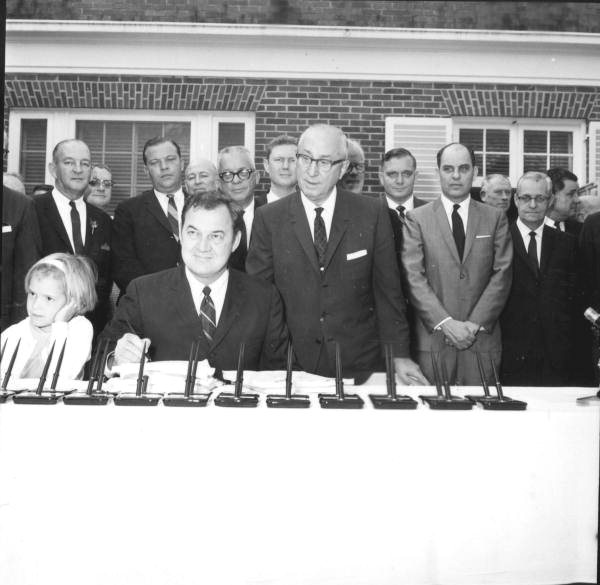 Roy Disney and group watching as Governor Claude Kirk signs the Disney bill at the Governor's mansion - Tallahassee, Florida.