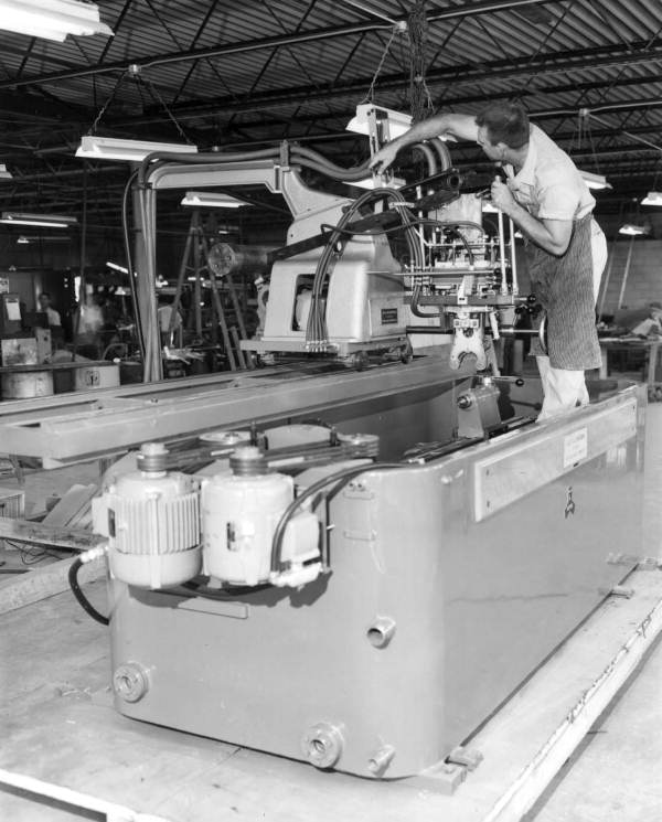 A worker making final check for crankshaft hardening machine before shipment - Tampa, Florida.