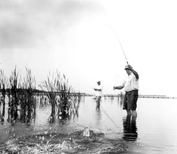 A man reeling in a fish at Deer Point Lake - Panama City, Florida.