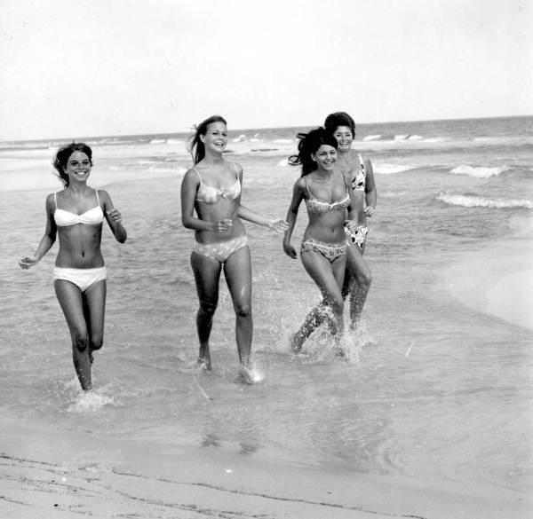 Four bikini clad women frolicking on the beach - Pensacola, Florida.