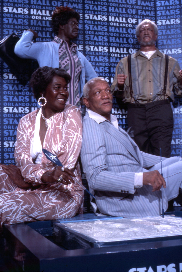 Actor Redd Foxx and actress LaWanda Page sitting with wax statues on display at the Stars Hall of Fame attraction in Orlando.