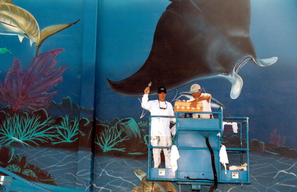 """Internationally recognized artist """"Wyland"""", at the left, during work on his mural."""