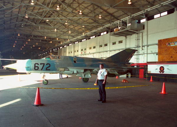 Assistant Fire Chief Dale McDonald posing with the Cuban MIG-21 parked inside building A-981 after defection to NAS Key West.
