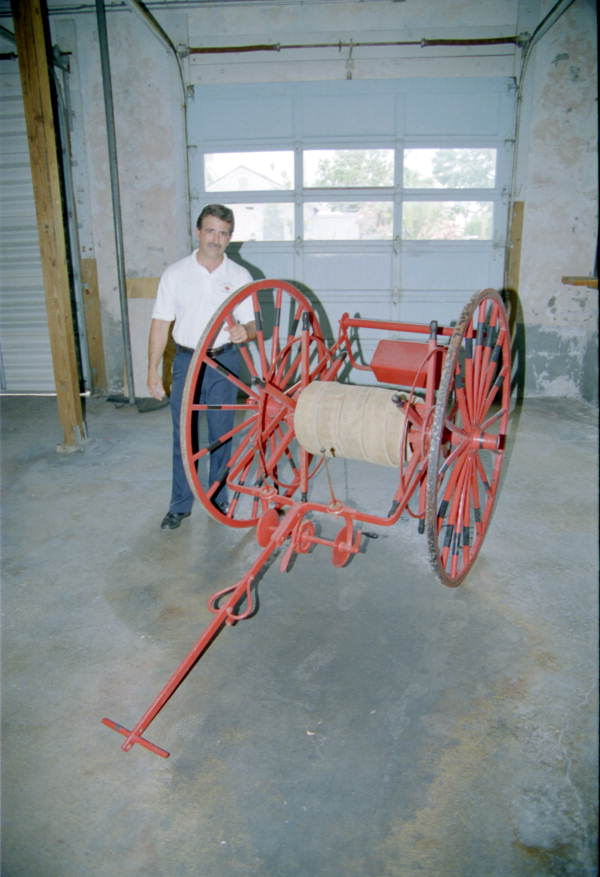 Alex Vega poses with old fire hose cart inside old Key West Fire Station #3..