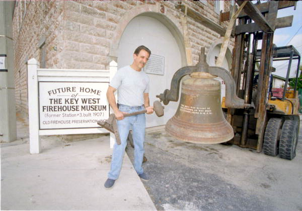 Key West Fire Department captain holding bell striker and posing with old fire house bell in front of museum - Key West, Florida.