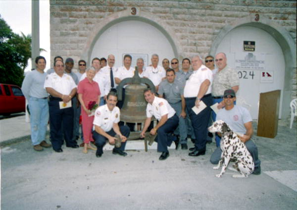 Group posing with the old KWFD fire bell following donation ceremony at the Fire House Museum - Key West, Florida}.