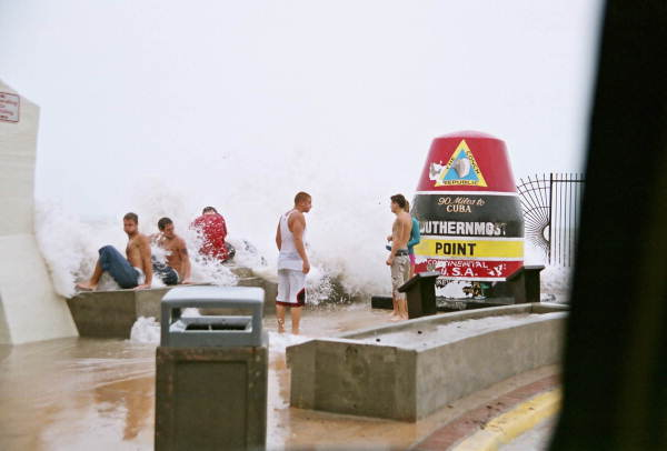 Young people enjoying storm waves at the Southernmost Point during Hurricane Rita - Key West, Florida.
