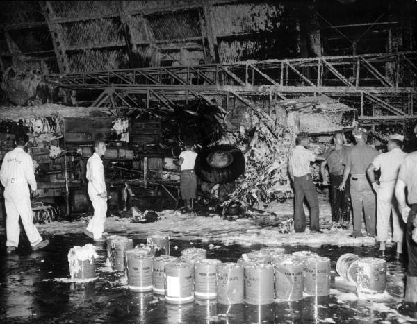 Key West Naval Air Station sailors looking over damage in hangar caused by a jet engine.