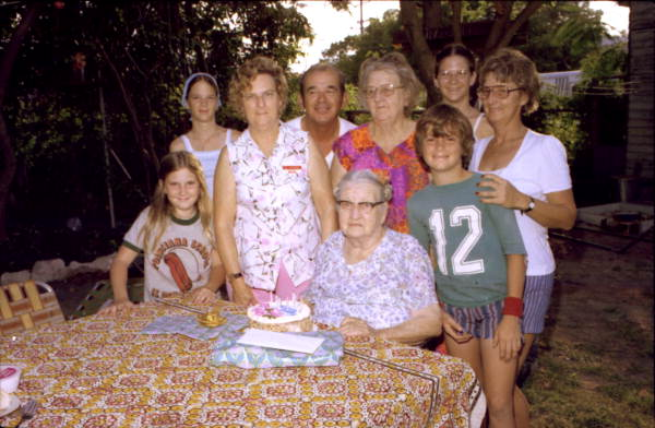 Clara McDonald seated at table with family members around her..