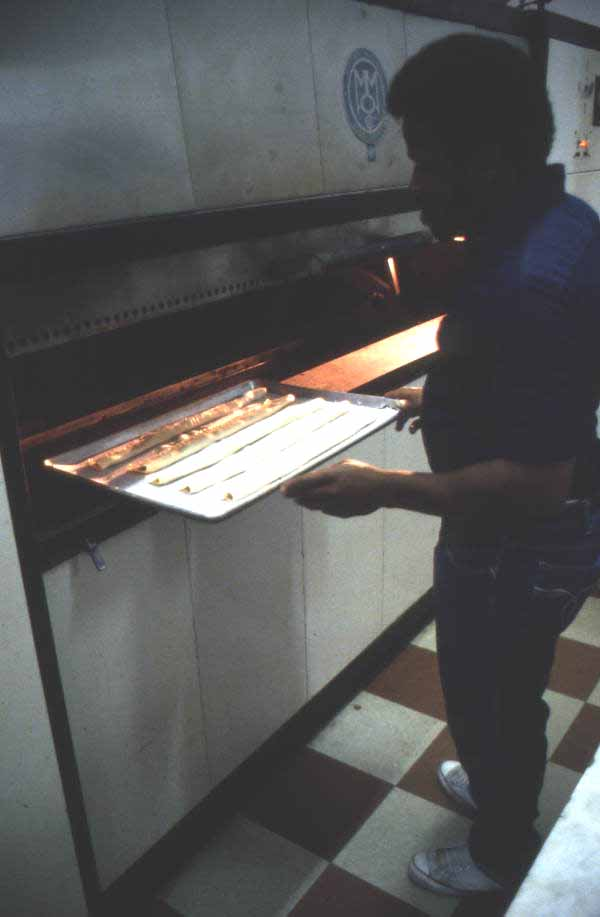 Jimmy Walton placing guava pastries into the oven - Jacksonville, Florida.