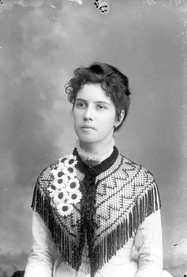 Woman draped in a bead shawl.