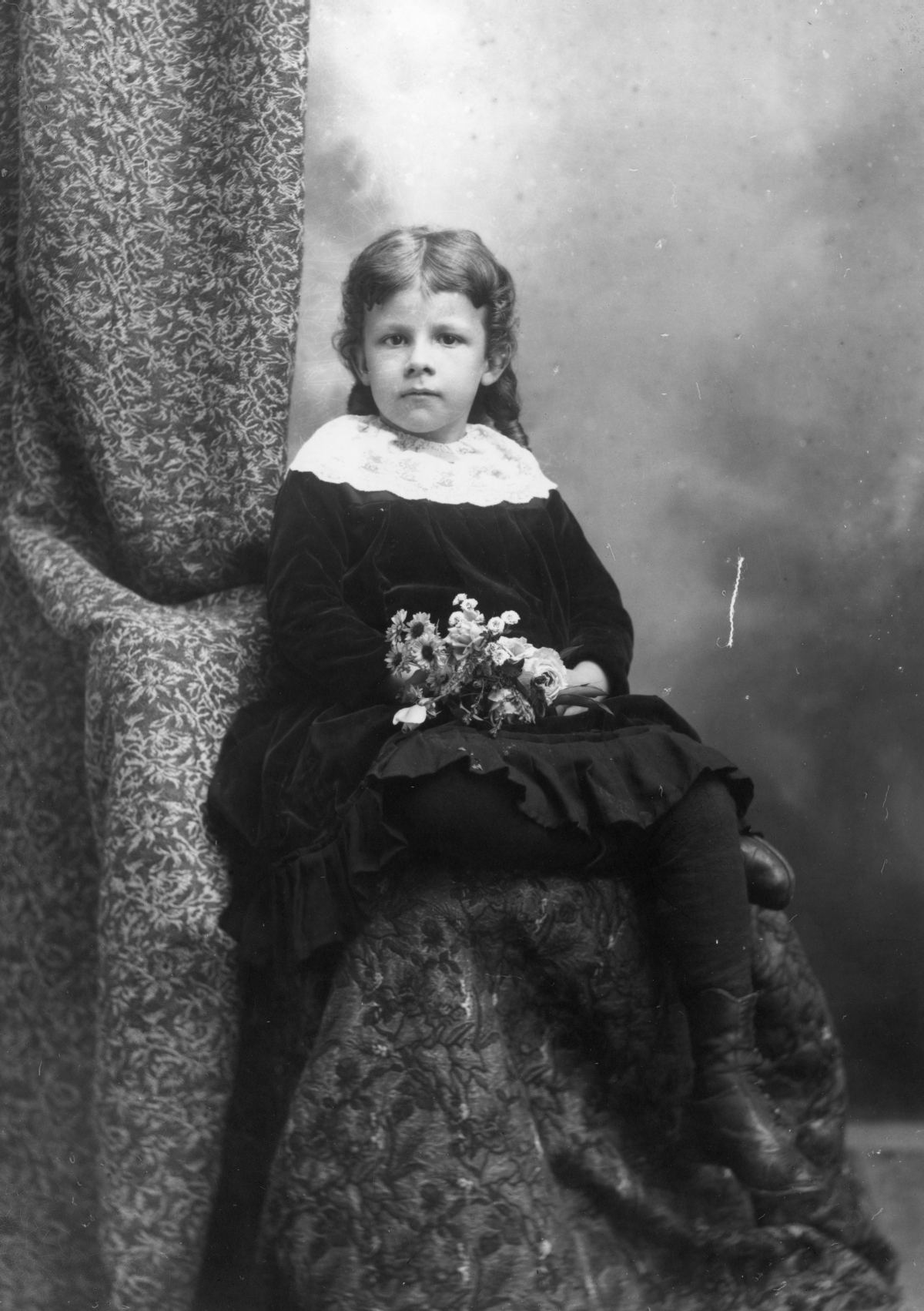 Seated girl holding a bouquet of flowers.