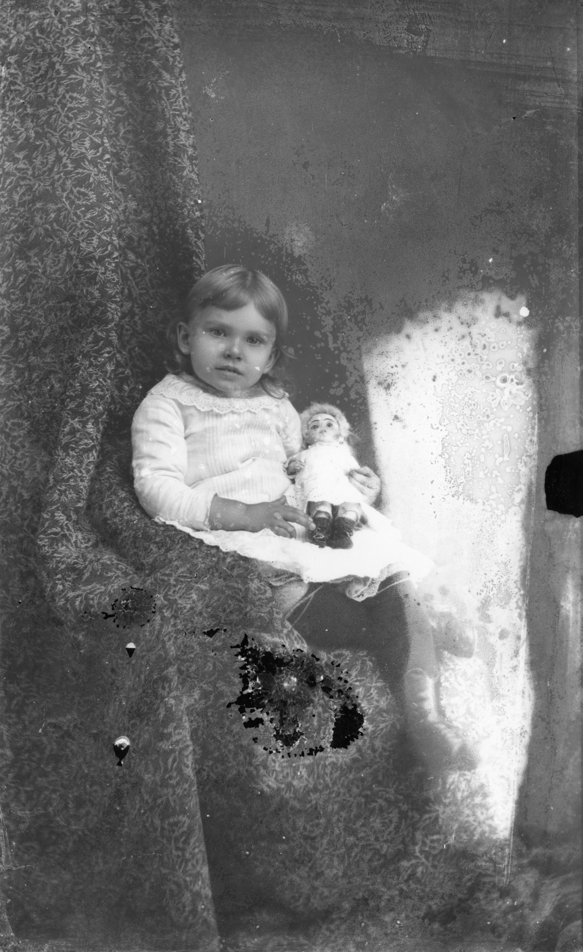 Girl holding a doll.